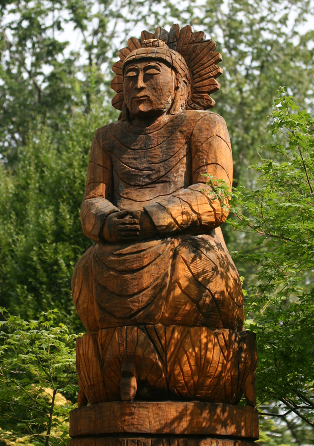 Buddha Sculpture 15 feet tall by chain saw carver in St. Louis garden designed by Linda Wiggen Kraft