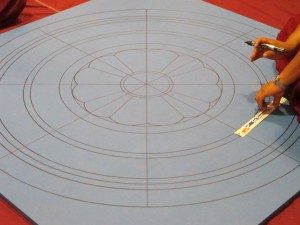 Tibetan Monks marking base for sand mandala for peace Saint Louis