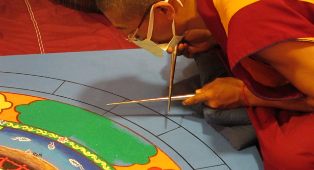 Tibetan Monk using chakpar to create Sand Mandala for Peace St. Louis