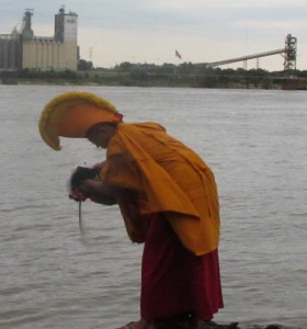Tibetan Monk pours sand from mandala into Mississippi River, St. Louis, photo by Linda Wiggen Kraft