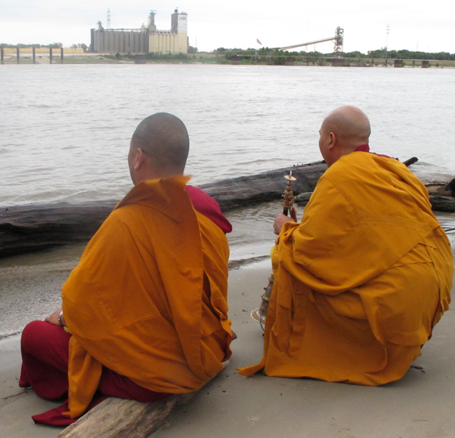 Tibetan Monks on shore of Mississippi River in St. Louis after putting sand from mandala into river, photo by Linda Wiggen Kraft